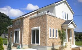 白い壁とレンガ調の外壁が上下に分かれたキュートな輸入風の家